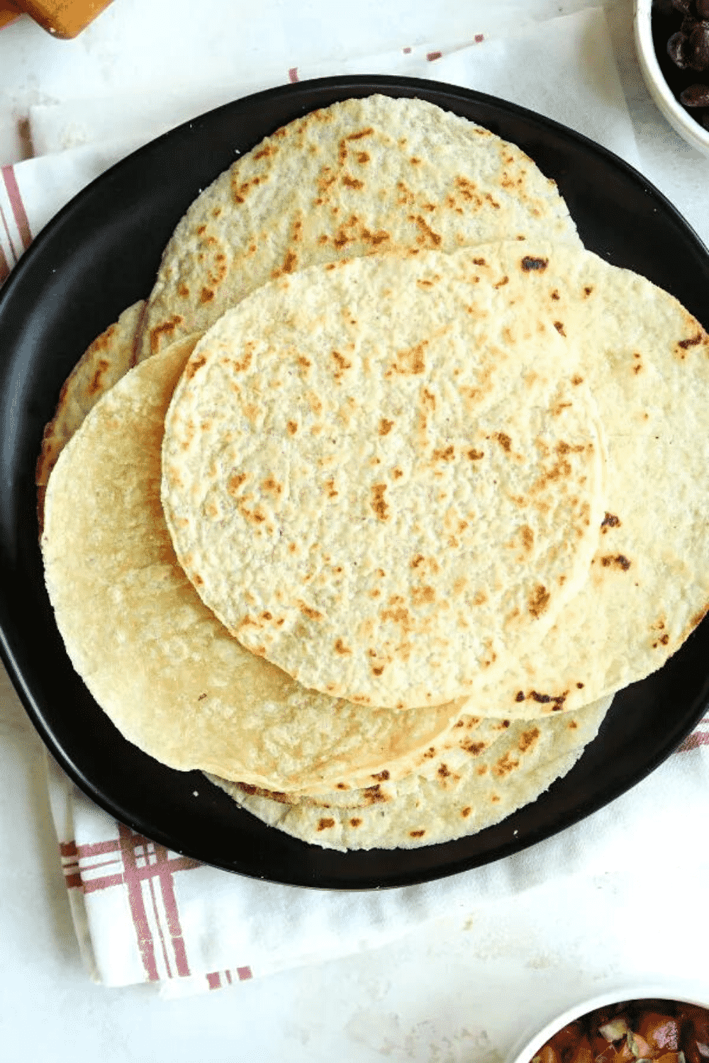 A bunch of keto tortillas stacked on top of each other on a black plate.