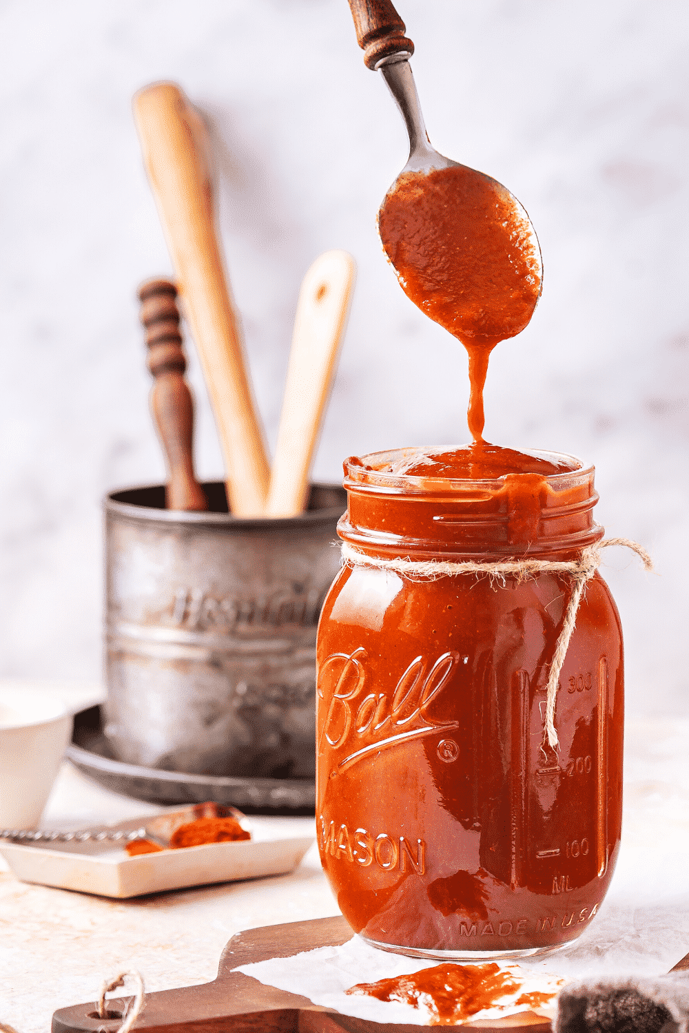 A glass jar filled to the top with BBQ sauce. A spoon is hovering over the jar dripping barbecue sauce down from it into the top of the jar.