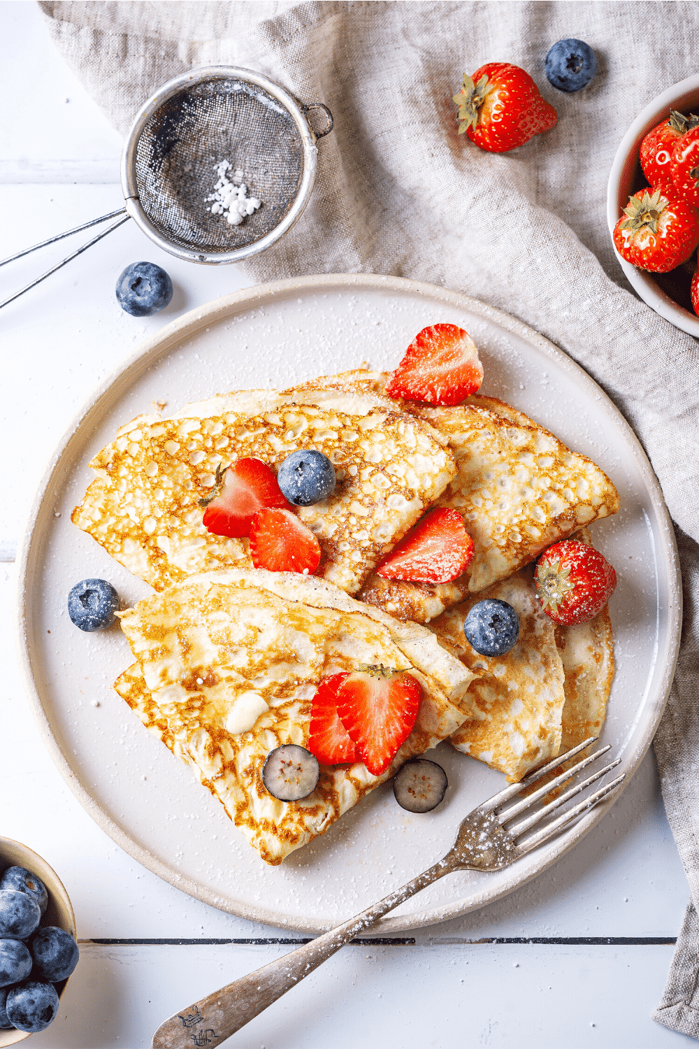 For crêpes overlapping one another on a white plate. They are slices of strawberries and blueberries on top of the crepes.
