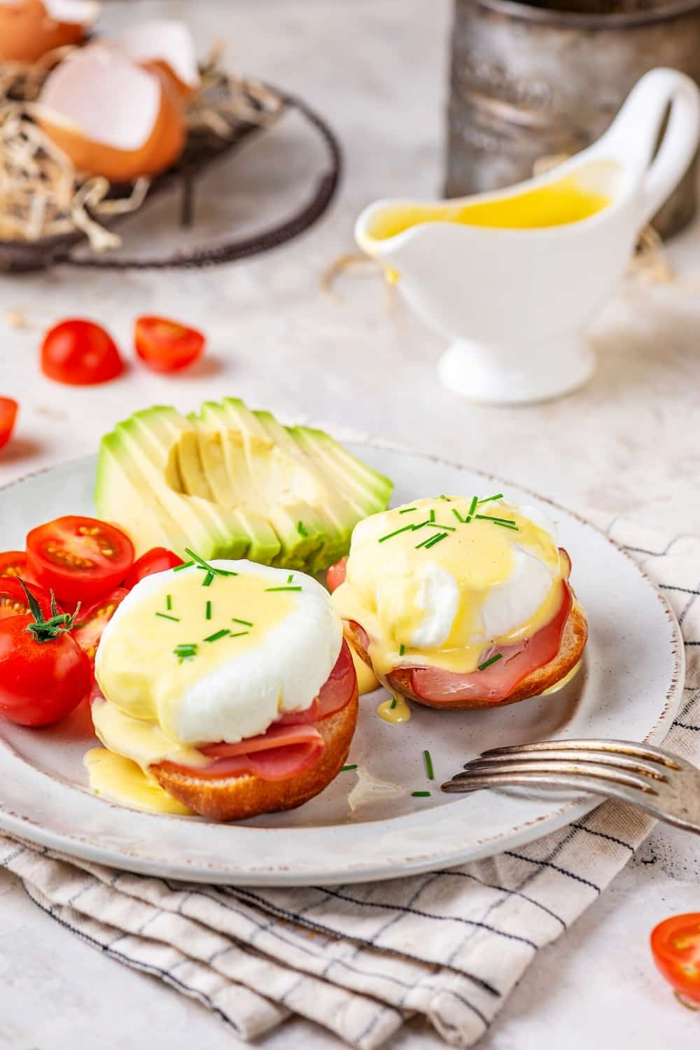 Two eggs benedict on a white plate with sliced tomatoes and a sliced avocado behind it. There is a gravy boat filled with hollandaise sauce behind it.