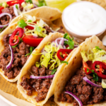 Three ground beef tacos in a horizontal row on a piece of newspaper on a white plate. Small cup of sour cream is behind tacos.