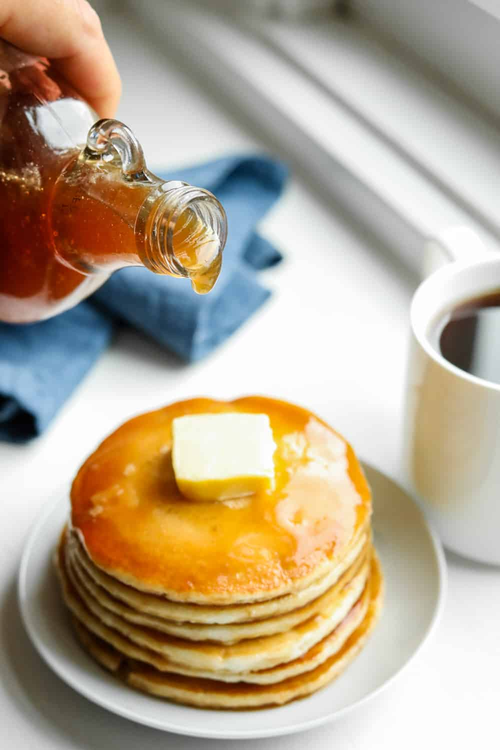 Maple syrup just about to be poured on a stack of pancakes.