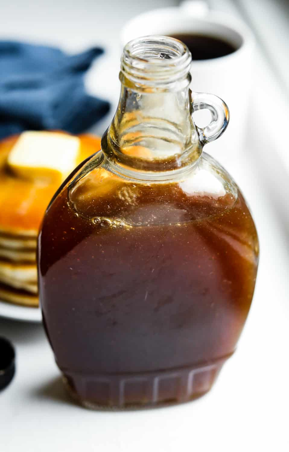 A bottle of maple syrup sat in front of a plate of pancakes, a blue napkin, and a cup of coffee.
