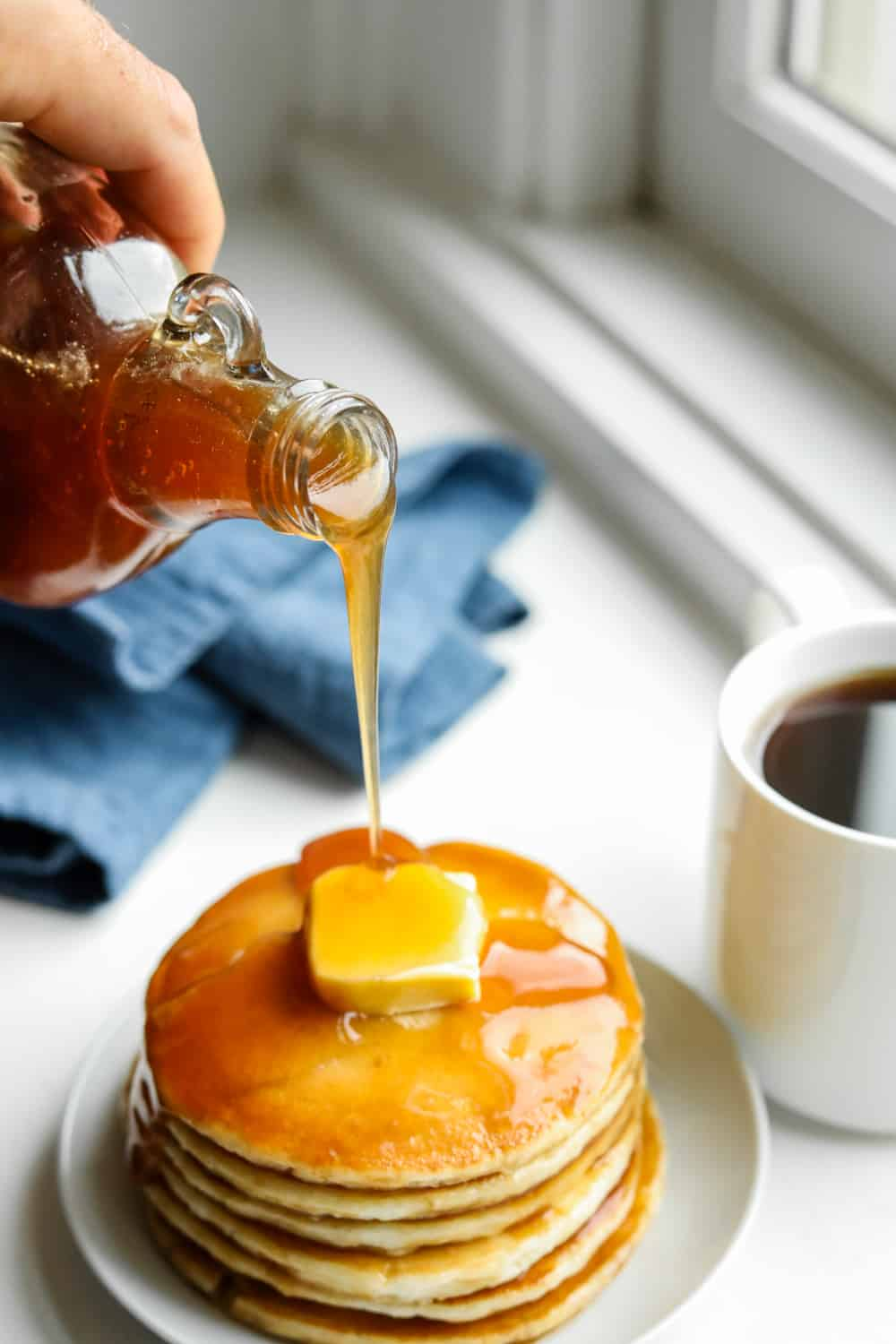 A hand holding a bottle of maple syrup and pouring it over a stack of pancakes.