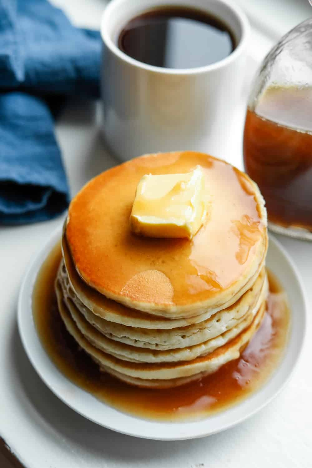 A stack of pancakes covered in maple syrup. There's a blue napkin a cup of coffee and a bottle of syrup behind the pancakes.