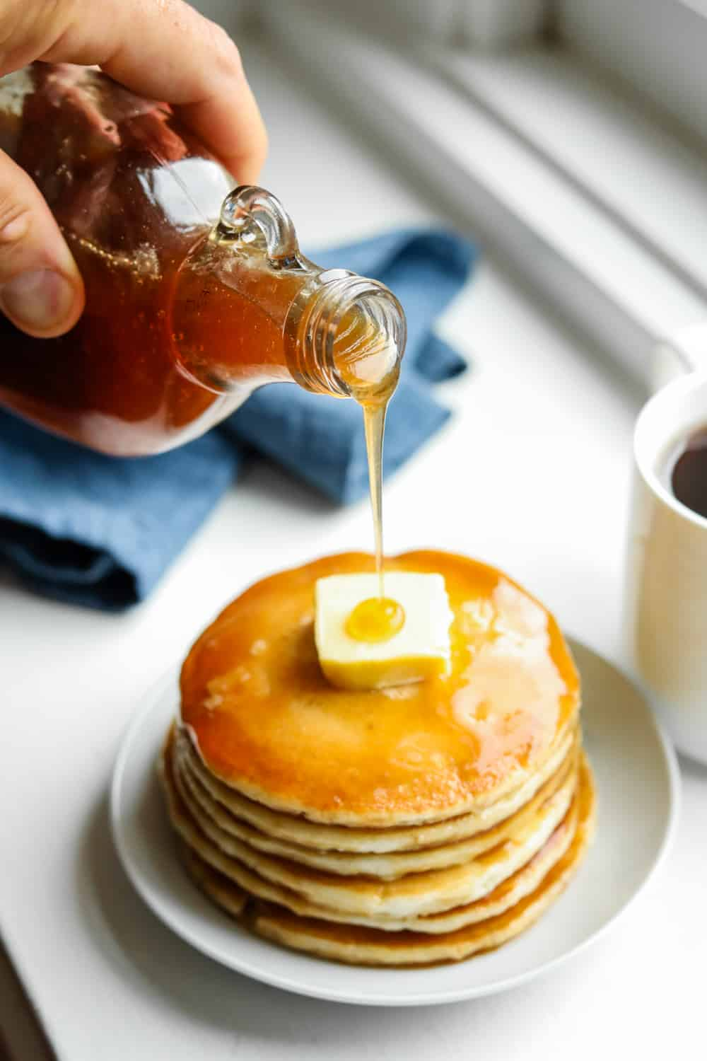 Maple syrup being poured on pancakes.