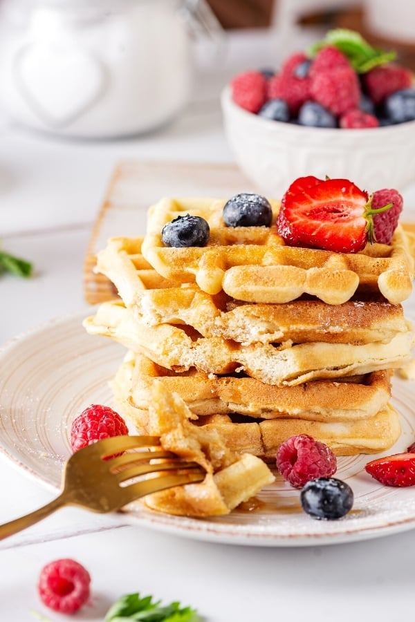 Stack of five waffles on a white plate. There is a fork sat on the edge of the plate with part of two waffles on the prongs. A few raspberries and blueberries are on the waffle and plate and there is a bowl of raspberries and blueberries behind the plate.