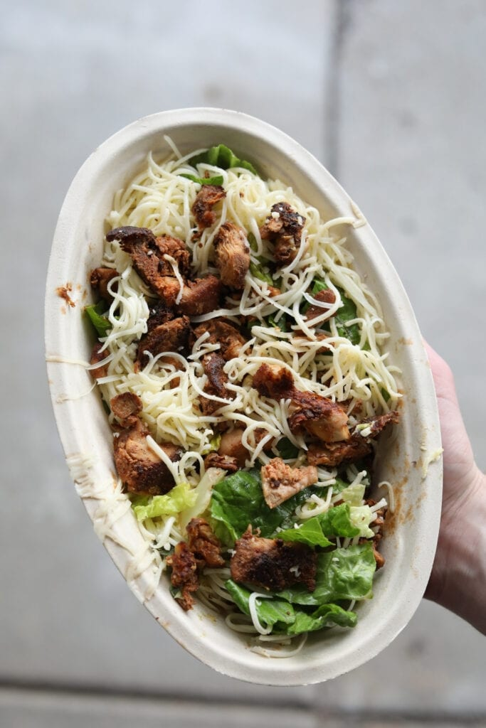 A hand holding a keto chipotle bowl with chicken, Romain lettuce, and shredded cheese.