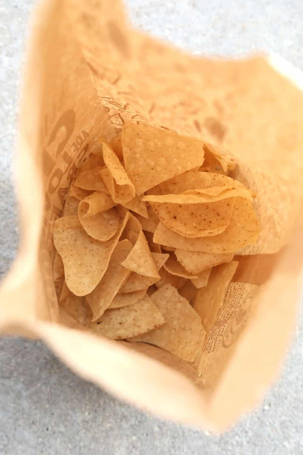 A brown bag filled with tortilla chips.