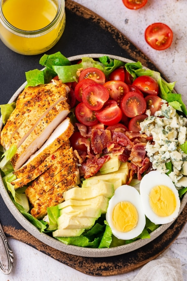A white play with Cobb salad on it. Part of a glass jar filled with Dijon vinaigrette dressing is behind the plate and both are on a serving board.