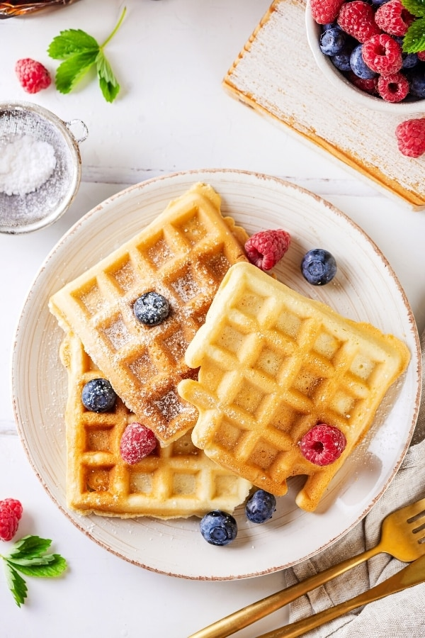 Three waffles on a white plate with a few blueberries and raspberries on top. Behind the plate is part of a bowl of blueberries and raspberries. In front of the plate is part of a golden fork and knife.