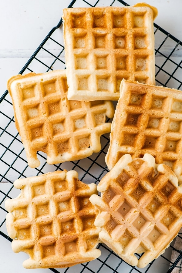Five keto waffles on a black wire rack.