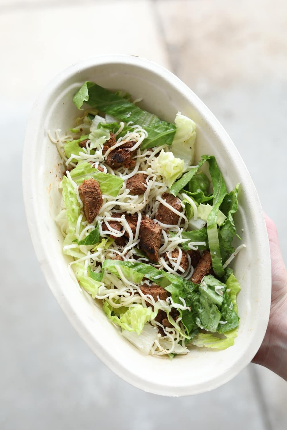 A hand holding a keto chipotle salad bowl with steak, lettuce, and shredded cheese.