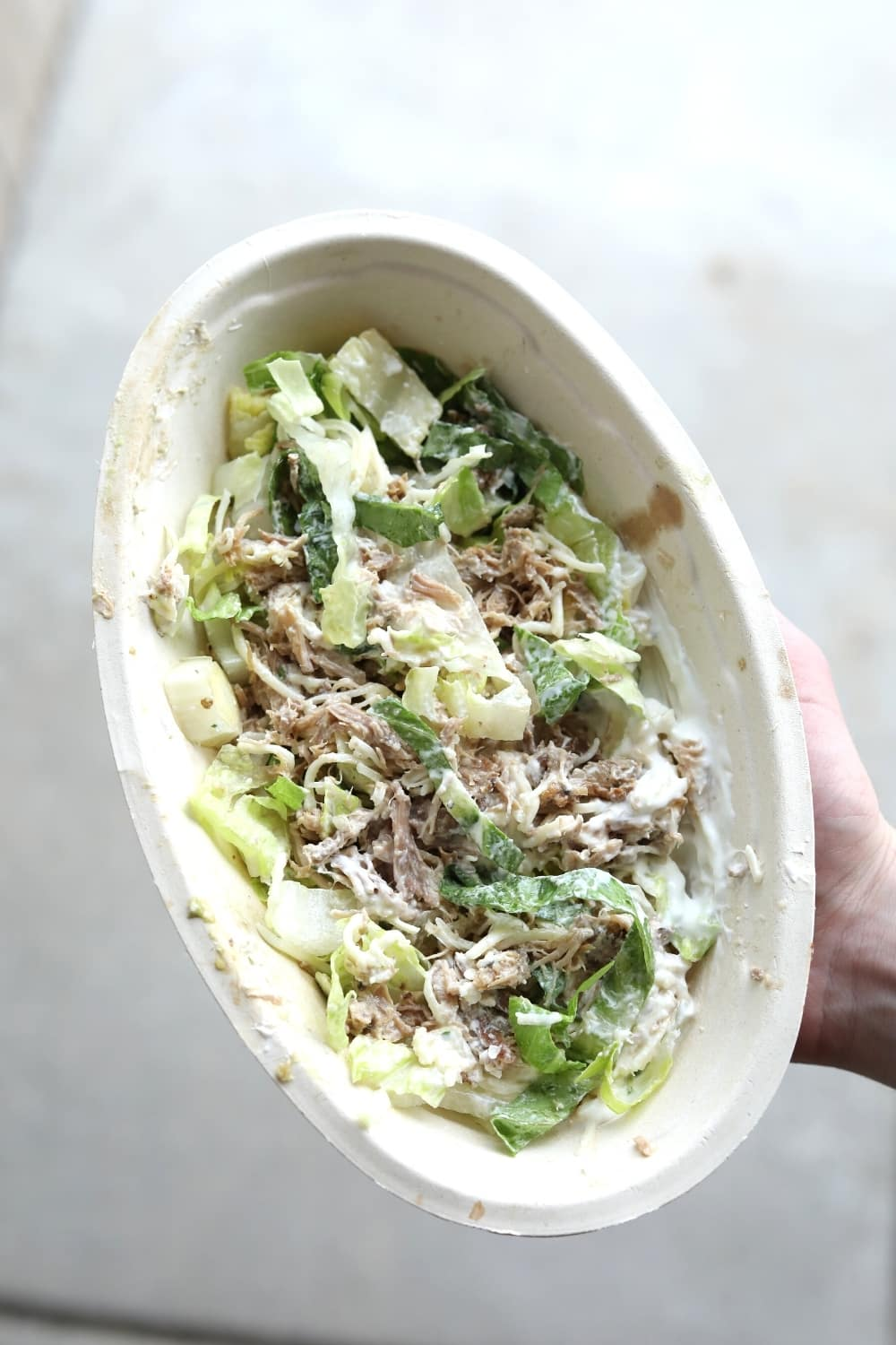 A hand holding a keto chipotle bowl with Carnitas, Romain lettuce, shredded cheese, and sour cream.