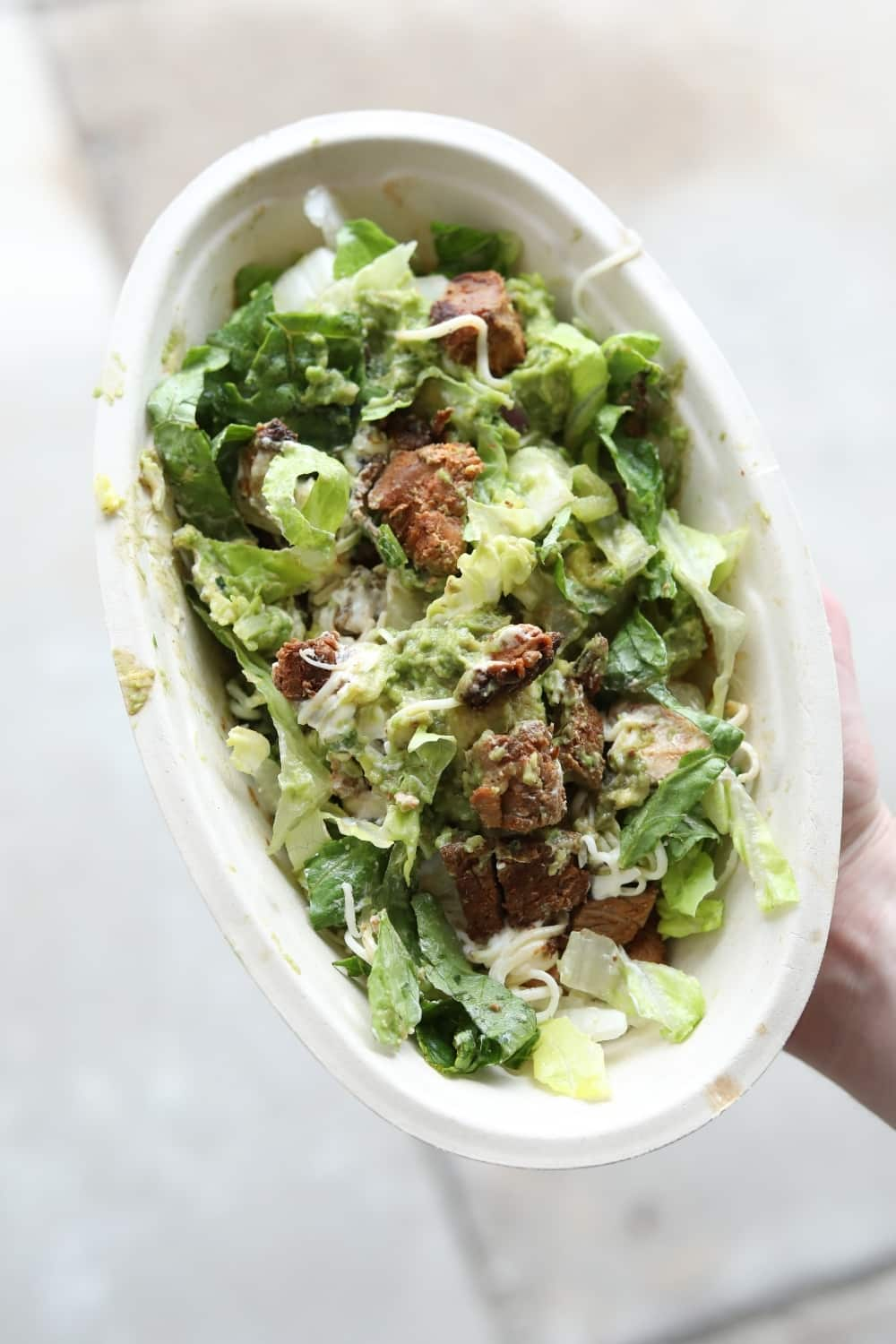 A hand holding a keto chipotle salad bowl with lettuce, steak, shredded cheese, and guacamole.