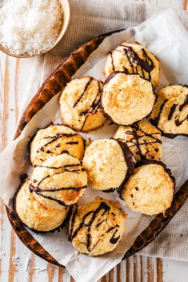 And oval bowl with white parchment paper in it with 11 coconut macaroons on top. Half of them have chocolate sauce drizzled on top and half of chocolate on the bottom of them. The bowl is on a gray tablecloth on a wooden table and behind tablecloth as part of a small bowl shredded coconut.