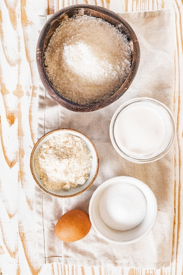 A medium sized bowl of finley shredded coconut, a small bowl of coconut flour in front of it, a small bowl of coconut milk to the right of it, and a small bowl of granulated erythritol and an egg. Everything is on a rectangular tablecloth on a wooden table.