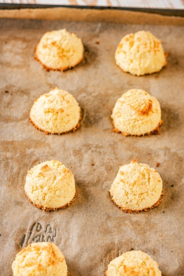 A baking sheet lined with brown parchment paper with two rolls of four coconut macaroons on it.