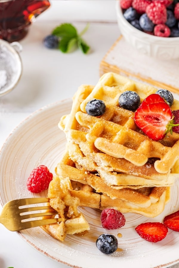 A stack of five waffles on a white plate with a few blueberries on the top waffle. The prongs of a fork is in front of the Stack with two pieces of waffle on it.