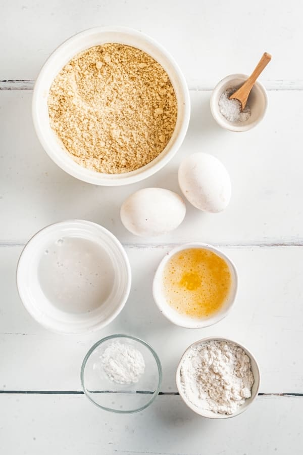 A white bowl of almond flour, two eggs, a small bowl of salt, a bowl of almond milk, a bowl of melted butter, a bowl of baking powder, and a bowl of granular swerve.
