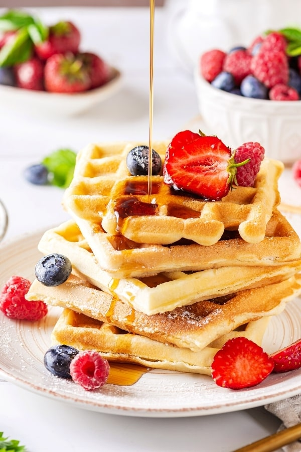 A stack of five waffles on a white plate. There is some maple syrup then drizzled over the waffles and a few raspberries, blueberries, and strawberries are on the waffles and plate.