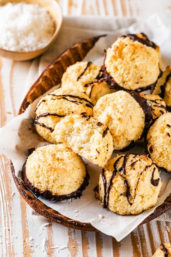 An oval brown bowl with a piece of parchment paper in it with a bunch of coconut macaroons on top. There is a bite out of one of the macaroons and several of them have chocolate sauce drizzled on top and others have chocolate on the bottom.