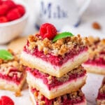 Three raspberry cheesecake bars stack on top of one another on a piece of white parchment paper. There are some raspberry cheesecake bars around the stack and part of a bowl of raspberries in the background.
