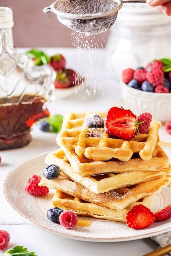 A stack of five waffles on a white plate. There is powdered sugar being sifted on the top of the waffles. There is part of a glass of maple syrup and a small bowl of blueberries and raspberries next to it.