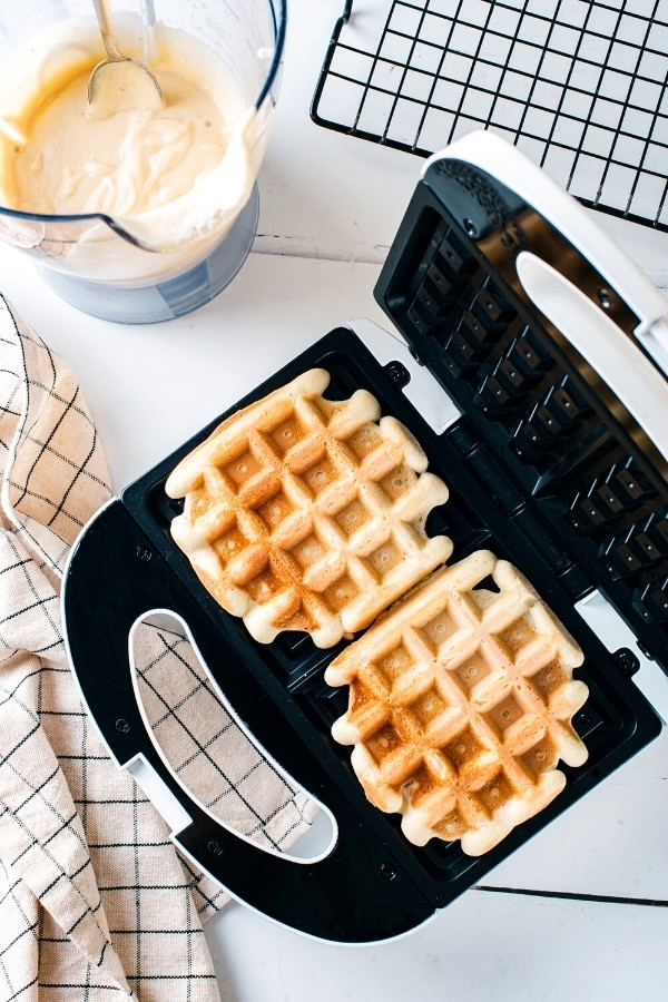 A waffle iron with two cooked waffles in it. Behind the iron is a blunder filled with waffle batter next to it as part of a black wire rack.