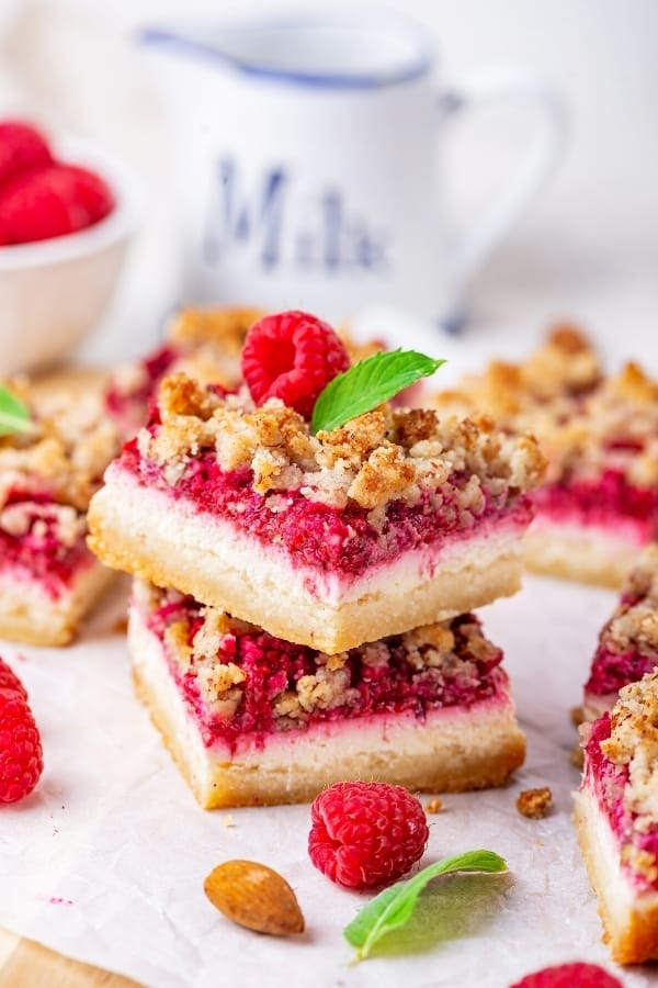 Two raspberry cheesecake bars stacked on top of one another on a piece of white parchment paper. There are parts of raspberry cheesecake bars surrounding them.