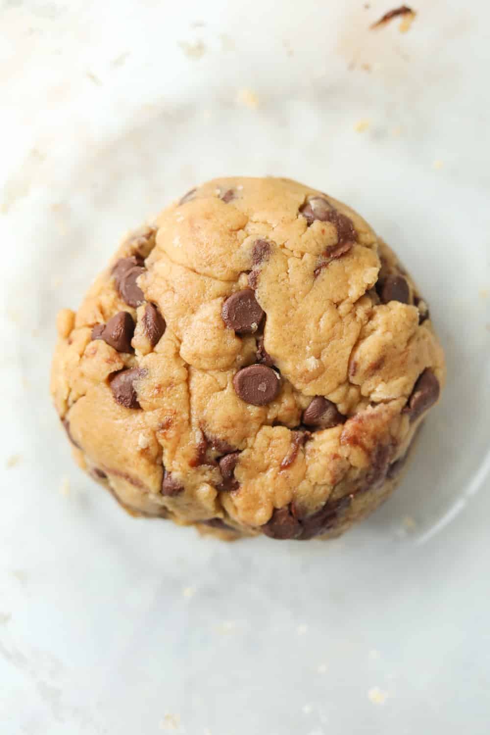 A ball of cookie dough in a clear bowl.