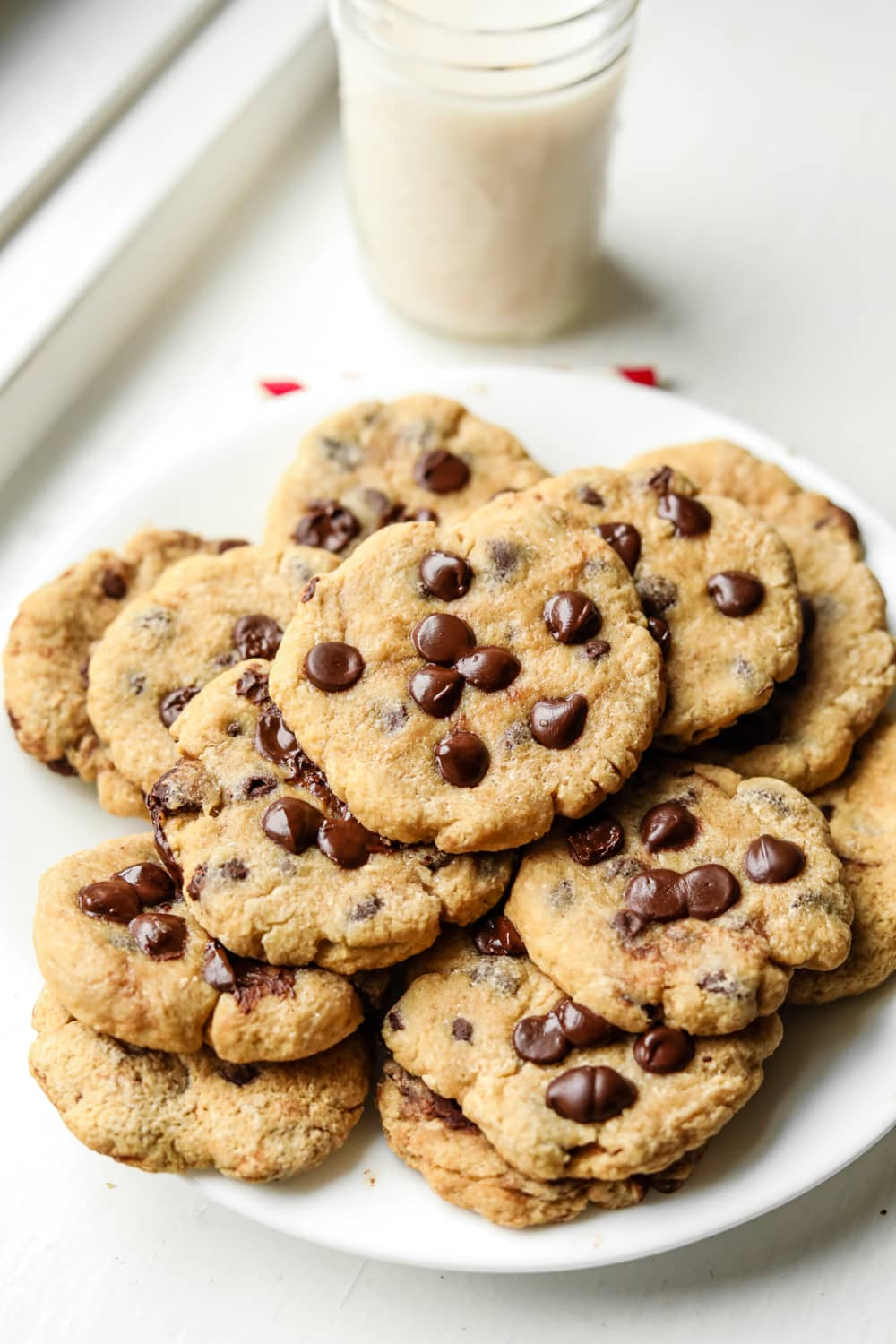 A white plate filled with chocolate chip cookies, and a glass of milk behind it.