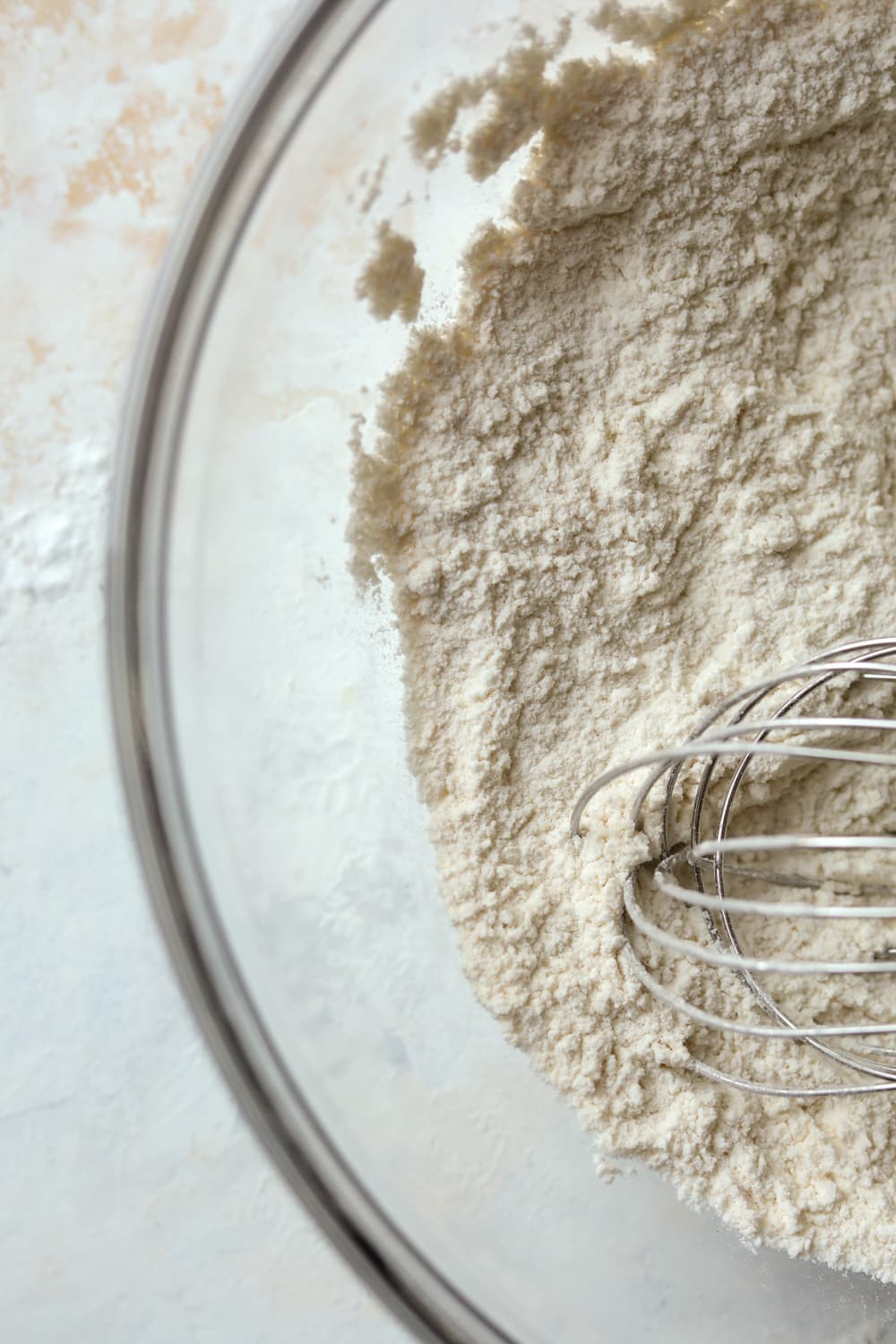A clear bowl filled with flour and a wire whisk.
