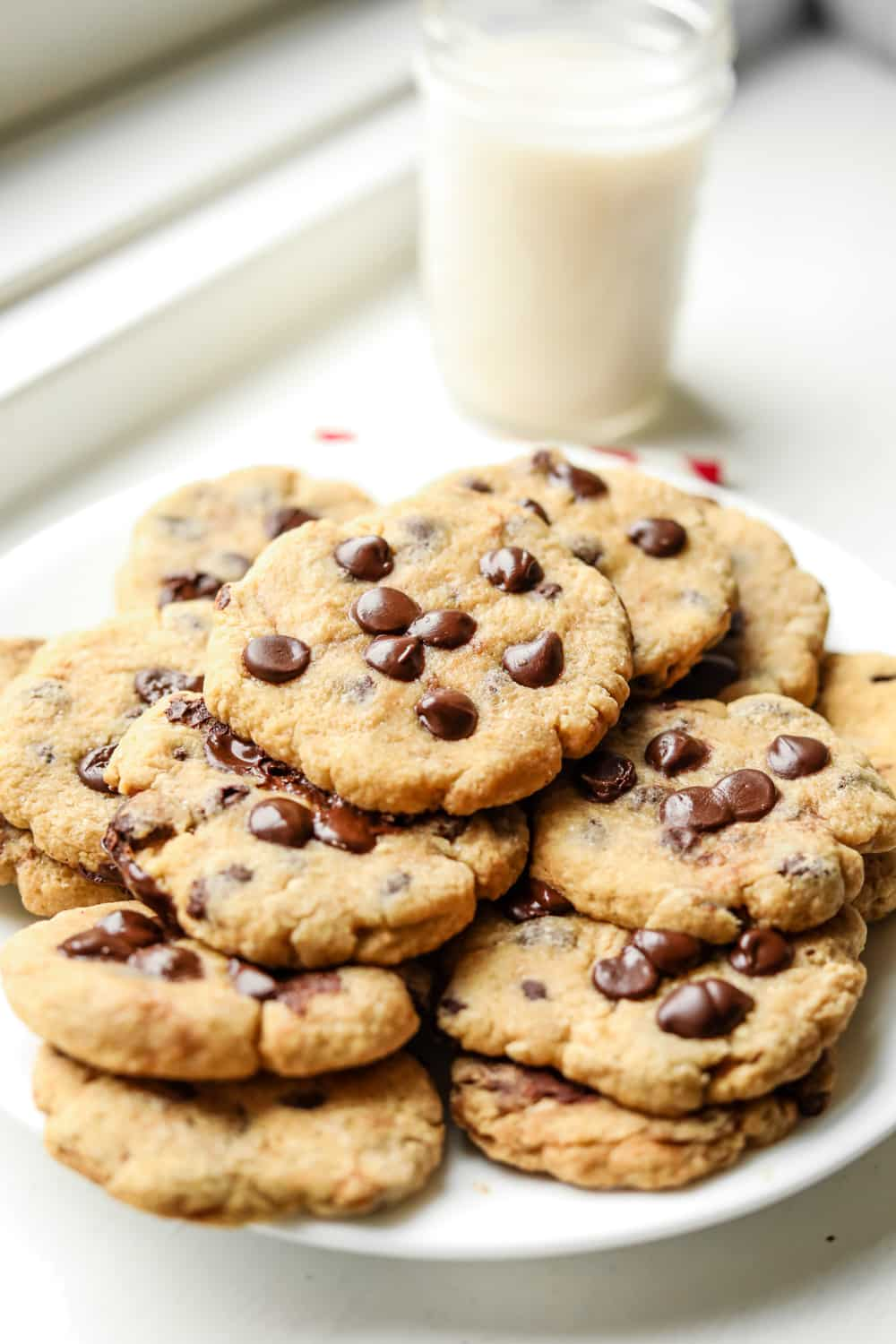 A plate of chocolate chip cookies with a glass of milk set behind the plate.