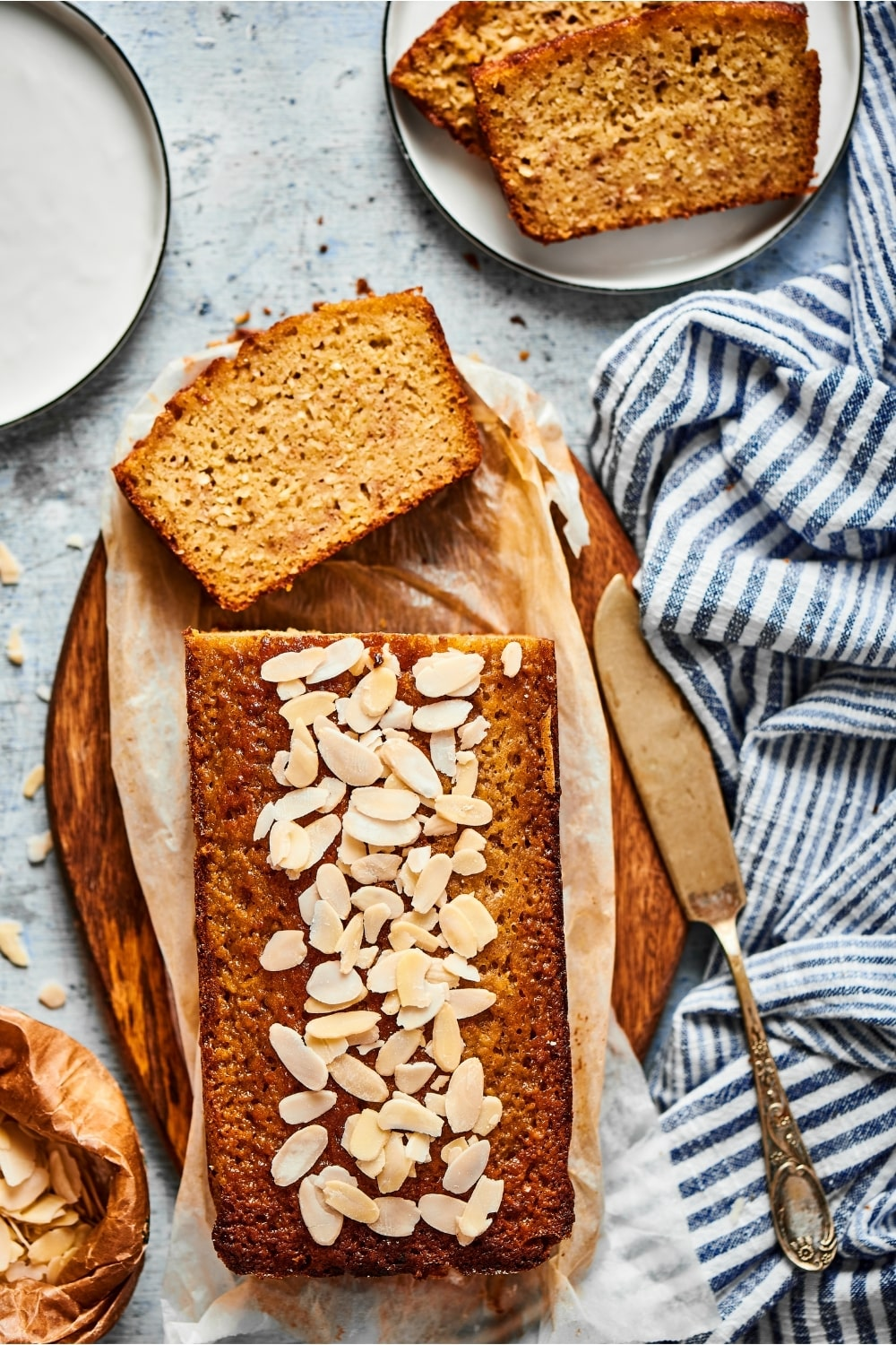 A loaf of banana bread and a piece of parchment paper on a wooden cutting board. There's a slice lying facedown in front of the loaf and in front of that is part of a white plate with two slices of banana bread on top of one another.