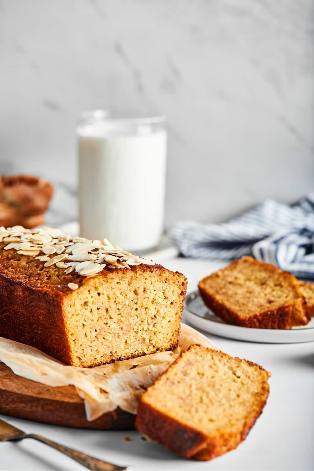 Part of a loaf of banana bread and a piece of white parchment paper on a wooden cutting board. A slice of banana bread is cut out and it is lying face down in front of the cutting Board. Behind the low is a glass of milk and a white plate with a slice of banana bread on it.