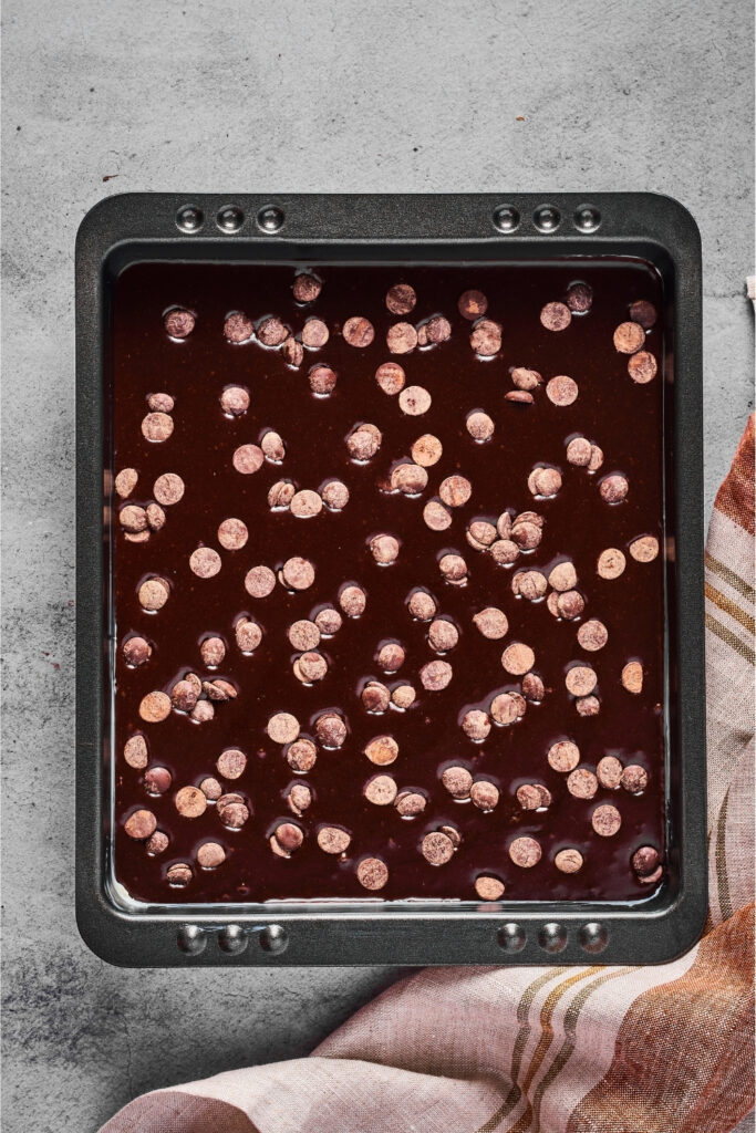 A baking tray filled with brownie batter with chocolate chips on top. The tray is on a gray counter.