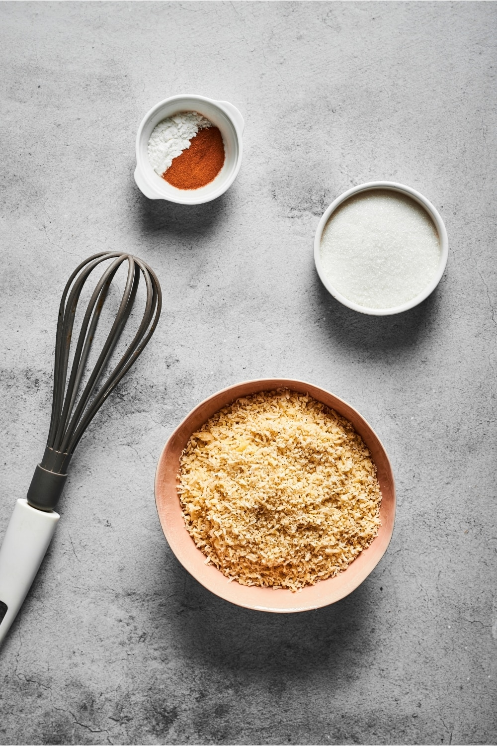 Small bowl of cinnamon and baking powder, a small bowl of confectioners erythritol, a small bowl of almond flour, and a whisk on a gray counter
