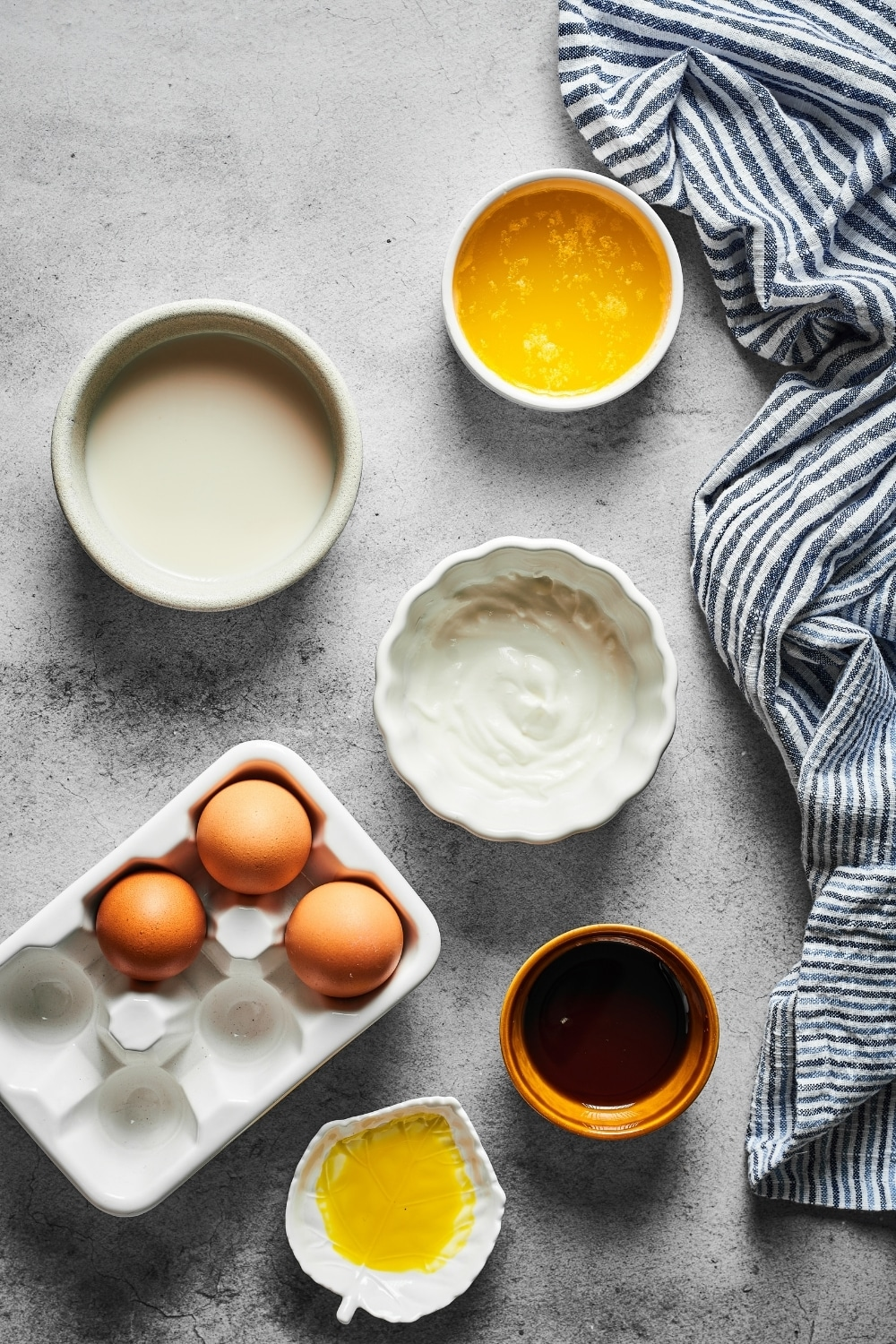 A small bowl of melted butter, a small bowl of milk, sour cream, banana extract, maple syrup, and three eggs all on a gray counter.