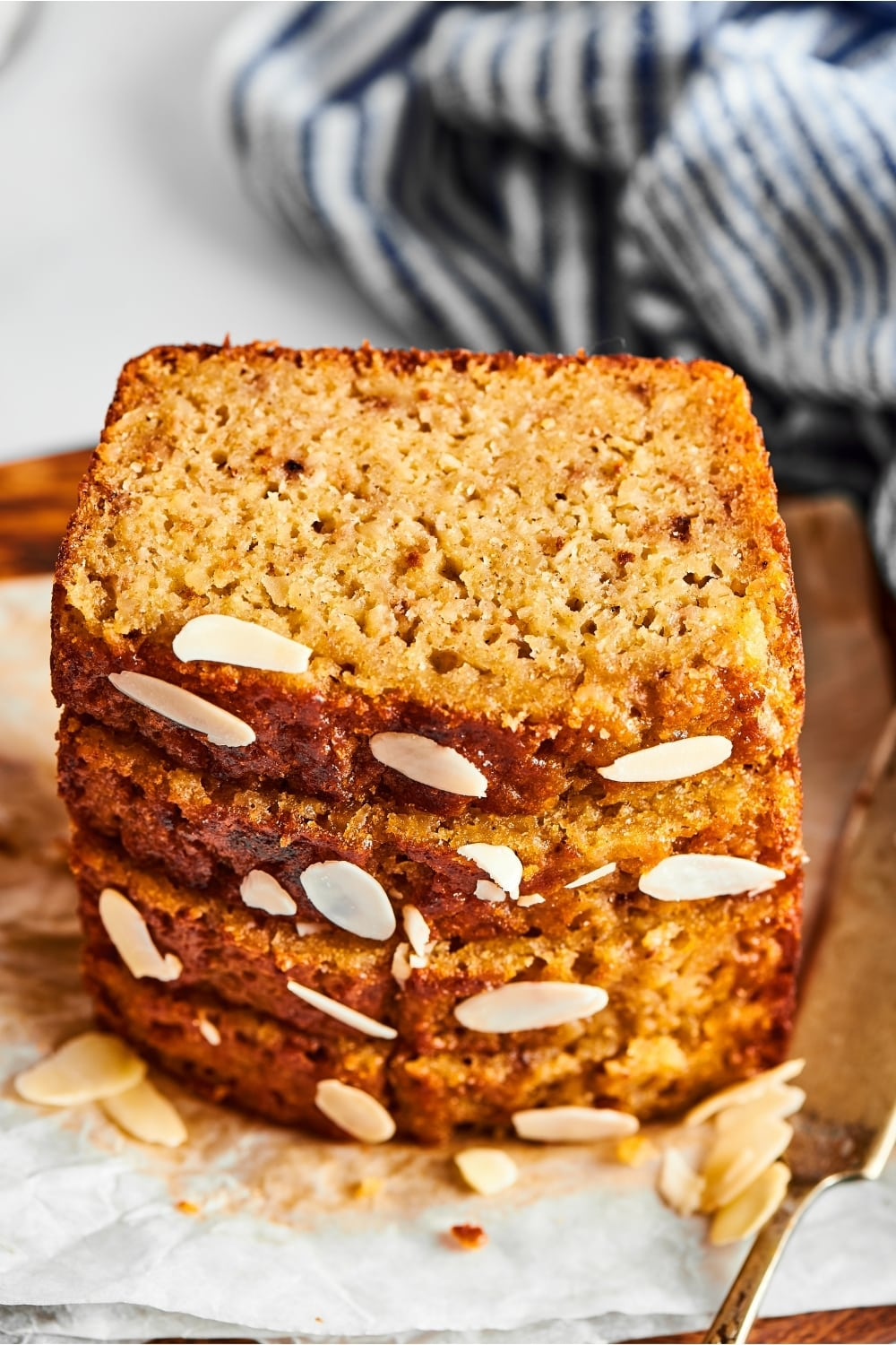 Four slices of banana bread stacked on top of one another on a piece of parchment paper. There are some sliced almonds in front of the Stack and part of a serving knife next to it.