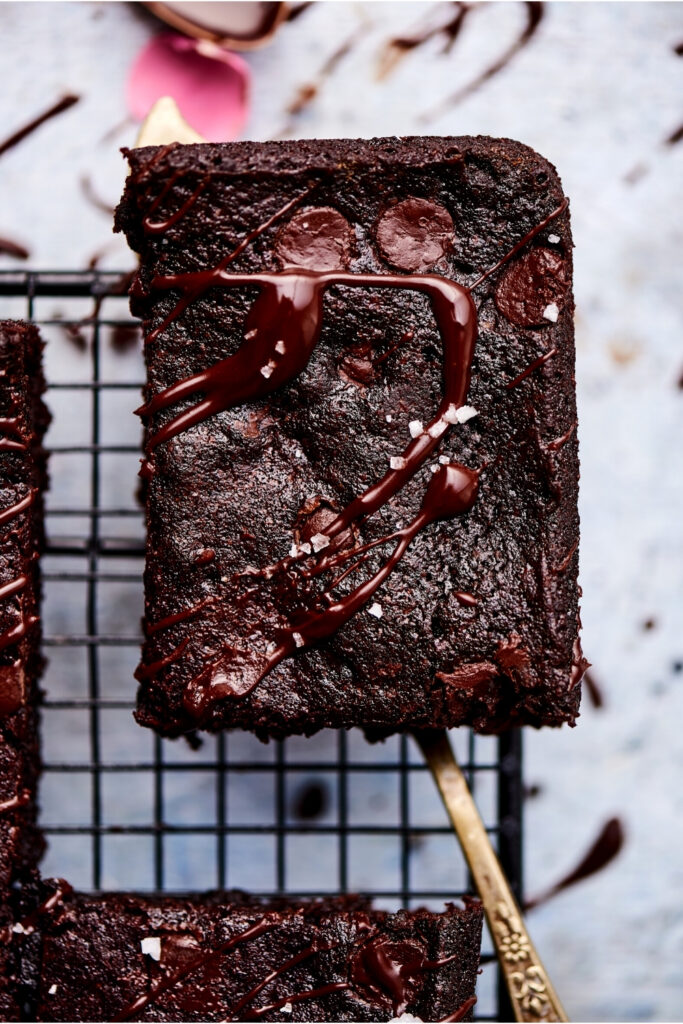 A Brownie is picked up by a serving spatula over a black wire rack.