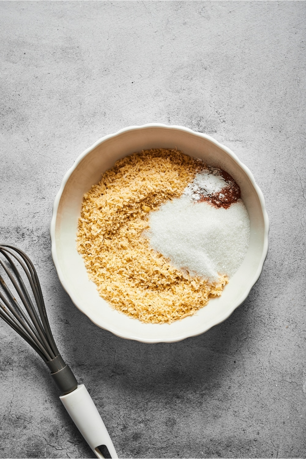 A small white bowl with almond flour, baking powder, cinnamon, and erythritol on a gray counter. There is a whisk to the left of the bowl.