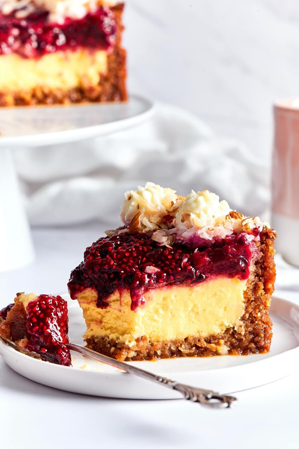 A slice of cheesecake on a white plate. There is a fork in front of the cheesecake with part of the cheesecake on it. Behind it is part of the cheesecake on a white serving tray.