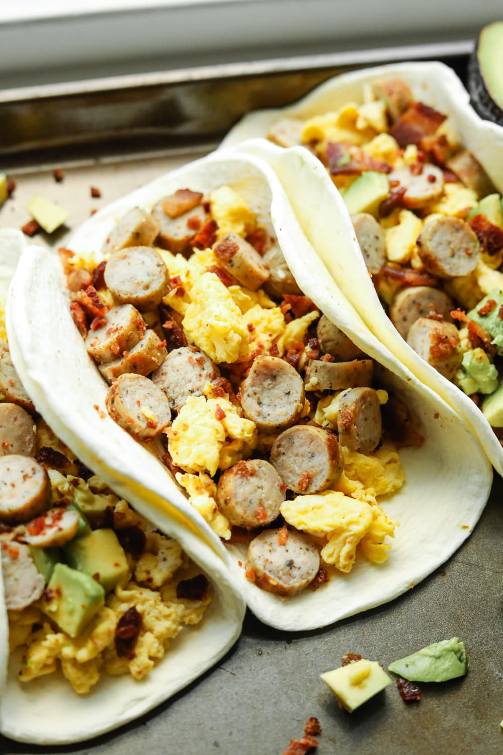 A baking sheet filled with breakfast tacos. The tacos have eggs, sausage, and bacon in them. Some of them have avocado as well.