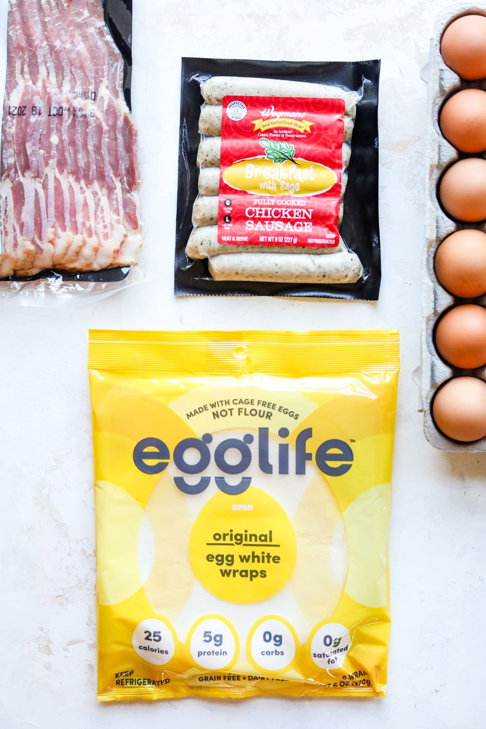 Egg wraps, breakfast sausage, eggs, and bacon on a white table. The ingredients are still in their packages & containers.