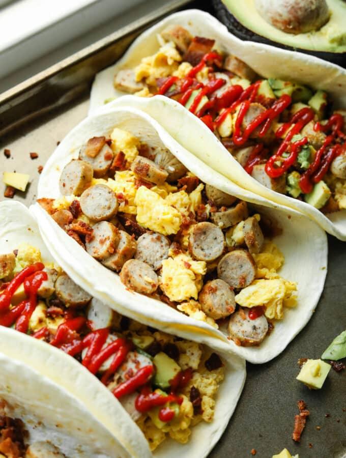 Several breakfast burritos on a gray baking tray.