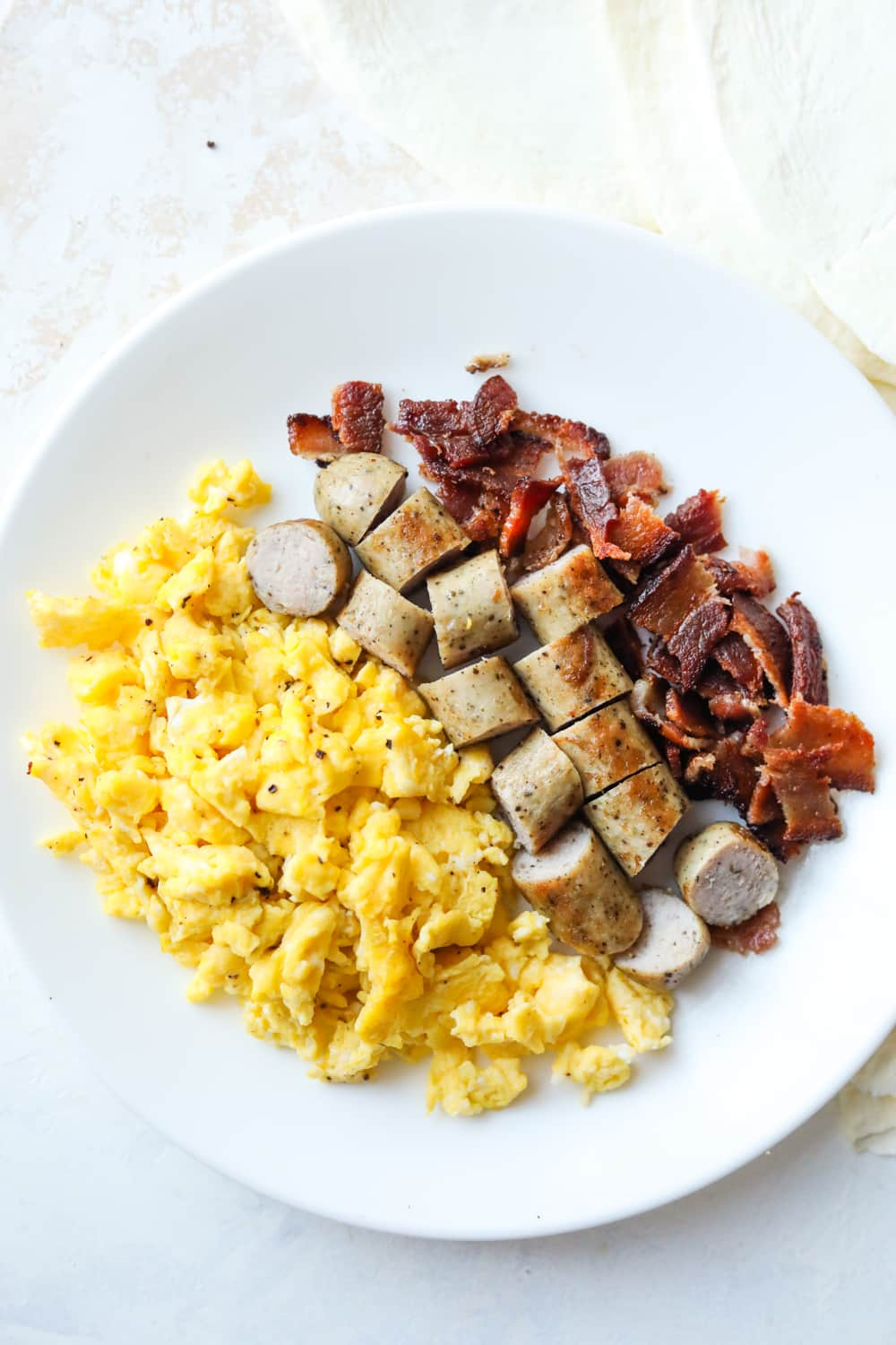 A white plate that is full of scrambled eggs and chopped bacon & sausage.