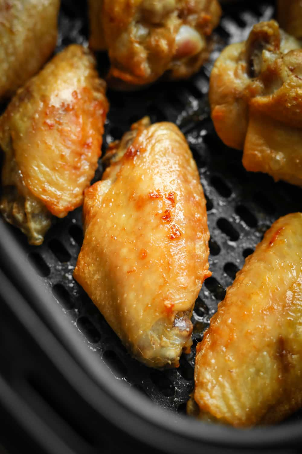 Chicken wings in an air fryer basket that have had multiple intervals of cooking and are ready to be sauced.