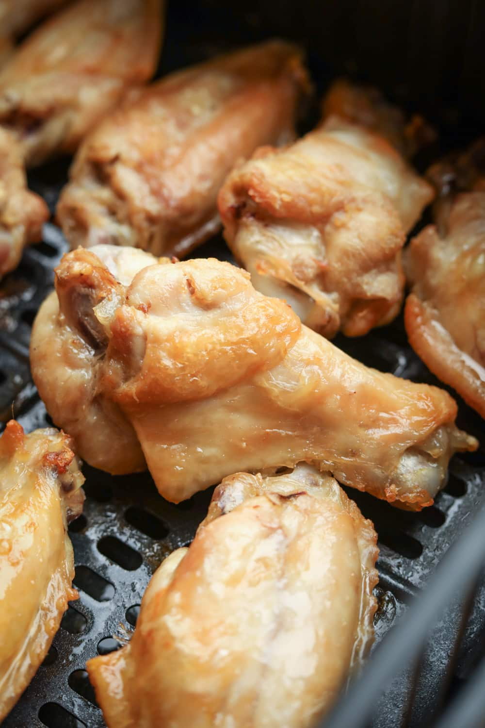 Chicken wings in an air fryer after one interval of cooking.