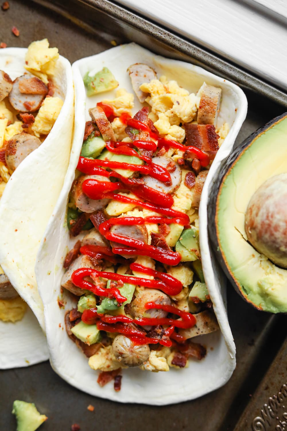 A white tortilla filled with eggs, sausage, bacon, and avocado, and topped with Sriracha.